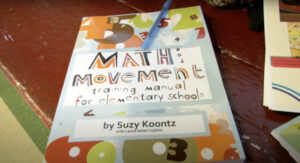 """A photo of the """"Math Movement Training Manual for Elementary Schools"""" by Suzy Koontz with Laura Gates Lupton"""